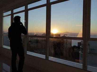 Homem na janela no por do sol - representando a empresa FX Capital